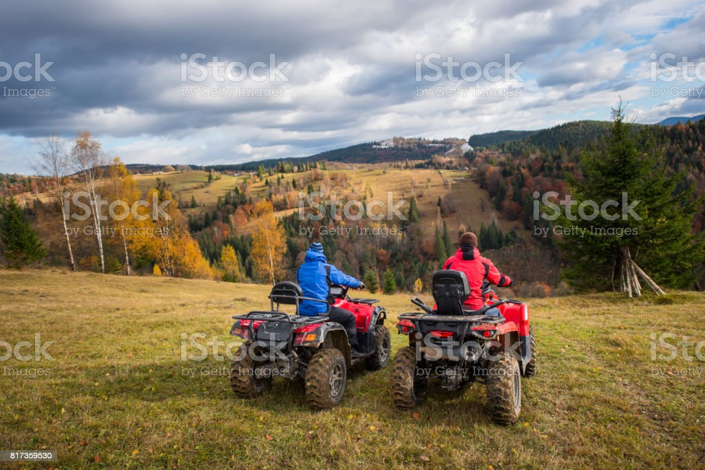 Rear view of two men sitting on quad bikes enjoying beautiful landscape of mountains and colorful forest under the sky with cumulus clouds in autumn stock photo