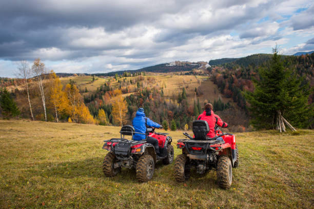 Rear view of two men sitting on quad bikes enjoying beautiful landscape of mountains and colorful forest under the sky with cumulus clouds in autumn Rear view of two men sitting on quad bikes enjoying beautiful landscape of mountains and colorful forest under the sky with cumulus clouds in autumn quadbike stock pictures, royalty-free photos & images