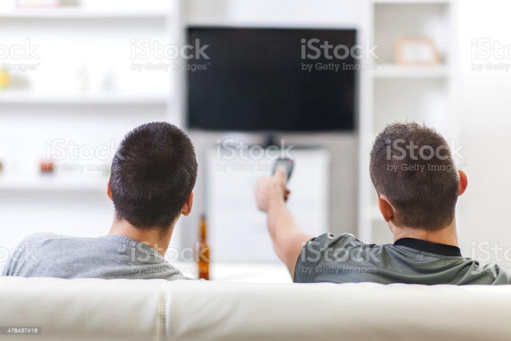 Rear view of two men watching TV at home. stock photo