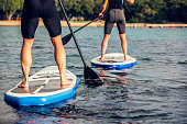 istock Rear view of two paddle boarder's legs 675298040