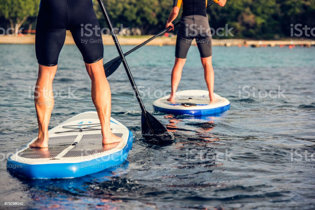 Rear view of two paddle boarder's legs стоковое фото