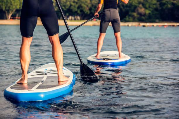 ansicht von hinten von zwei paddel boarder es beine - stehpaddeln stock-fotos und bilder