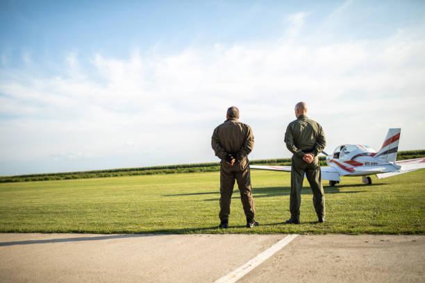 rückansicht von zwei piloten auf wiese - flugschule stock-fotos und bilder