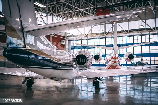 Small airplanes parked in a hangar.
