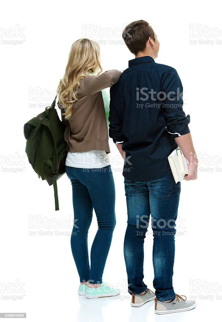 Rear view of two students holding books & standing stock photo