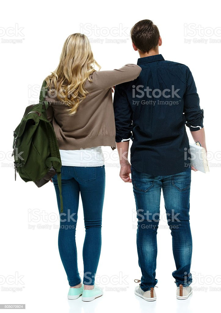 Rear view of two students standing together stock photo