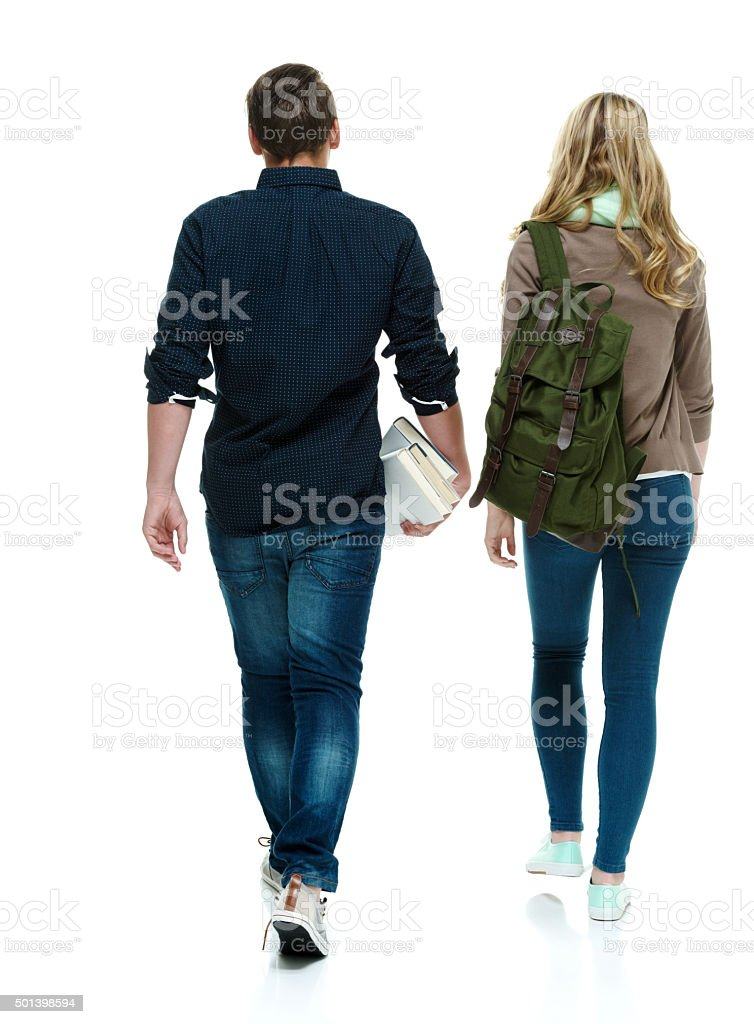 Rear view of two students walking stock photo