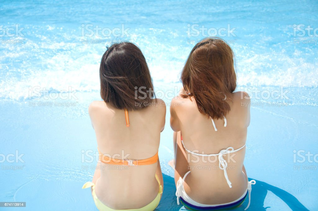 Rear view of two swimsuits women sit by the pool royalty-free stock photo