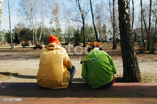 585604690 istock photo Rear view of two teenage boys sitting on a bench in a park wearing green and yellow hoodies, stooped, looking at their phones 1214271993