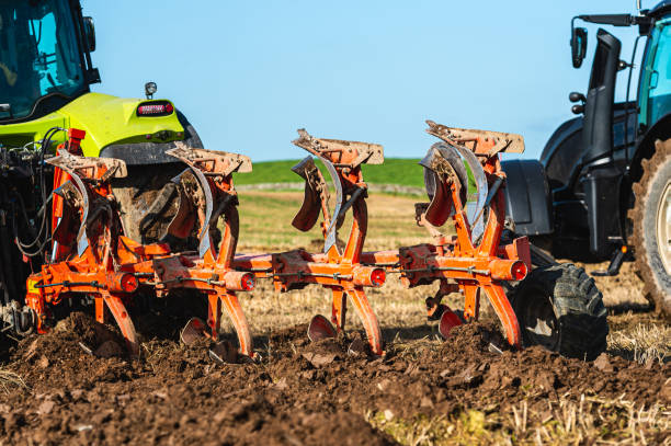 Rear view of two tractors ploughing in a field in Dumfries and Galloway south west Scotland A plough being used in late summer to prepare a field and make it ready to sow a new crop to harvest next year johnfscott stock pictures, royalty-free photos & images