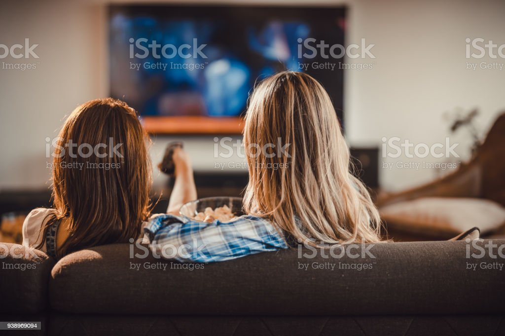 Rear view of two women relaxing on sofa in the living room and watching a movie on TV. stock photo