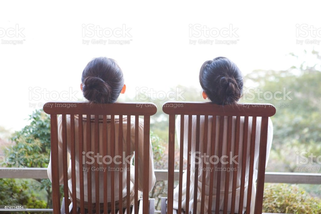 Rear view of two women sitting on a porch Chair royalty-free stock photo