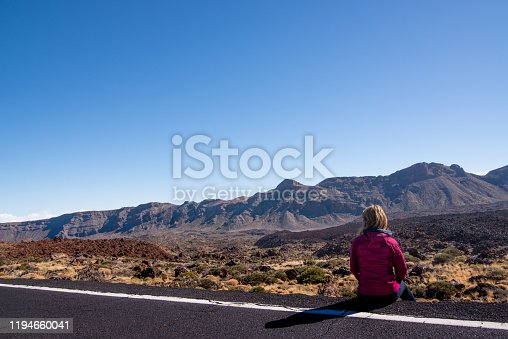 Rear View of Unrecognisable Woman Sitting on the Edge of the Road and Enjoying the Majestic Sight of Sendero de Montana Blanca, Tenerife, Canary Islands, Spain - stock photo