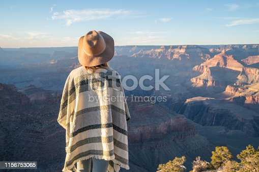 Rear view of unrecognisable woman standing above Grand Canyon on top of it all; girl with poncho and hat looking at landscape; fashionable internet people