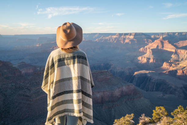 Rear view of unrecognisable woman standing above Grand Canyon on top of it all; girl with poncho and hat looking at landscape; fashionable internet people stock photo