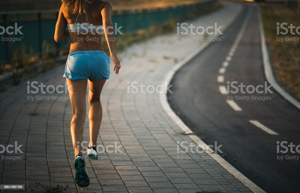 Rear view of unrecognizable athlete running on the street. royalty-free stock photo