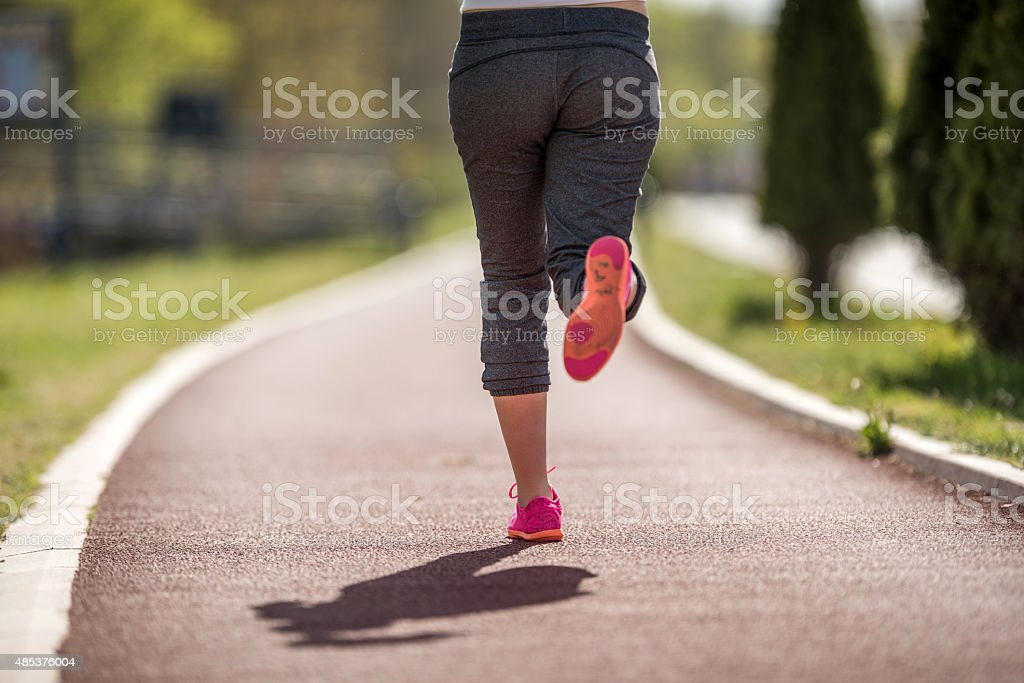 Unrecognizable person running on a running track.
