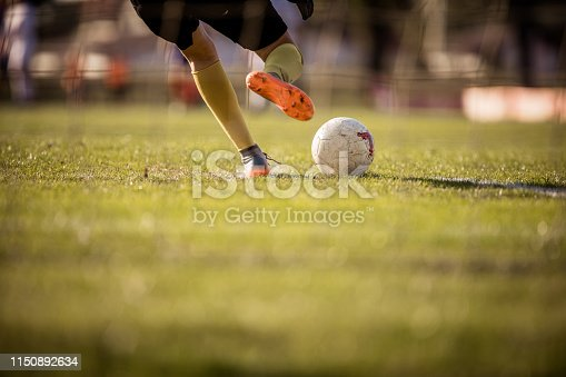 Back view of unrecognizable female goalkeeper kicking soccer ball on playing field. Copy space.