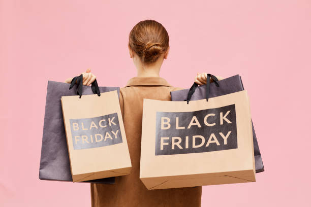 Rear view of unrecognizable woman with hair bun carrying black Friday paperbags on shoulders while leaving store stock photo