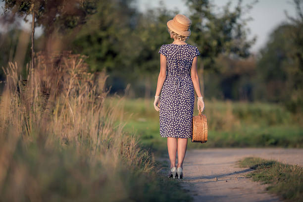 Rear view of vintage 1920s summer fashion woman wearing dress. stock photo