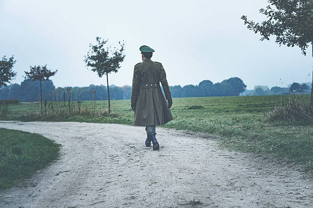 Rear view of vintage 1940s military officer walking on road. – Foto