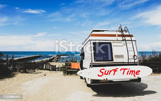 Rear view of vintage camper parked on the  beach against a beautiful scenic view - Caravan of surfer with a surfboard on back - Nomadic life concept of surfer waiting for better waves - Surf Time text