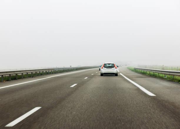 bakifrån av vita volvo på motorvägen dimma dag - volvo bildbanksfoton och bilder
