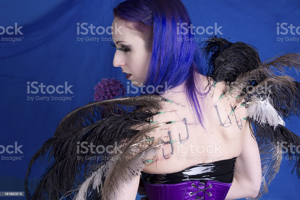 Rear view of winged woman in studio. stock photo
