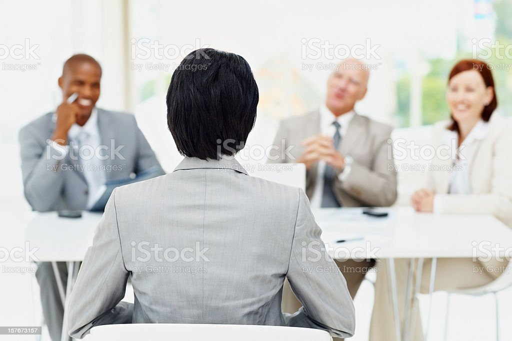 Rear view of woman being interviewed by diverse panel royalty-free stock photo