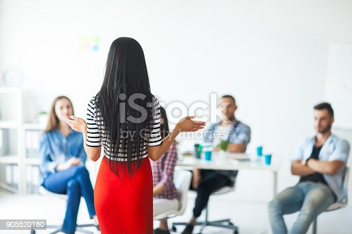618851838 istock photo Rear view of woman business coach gesturing with hand 905520180