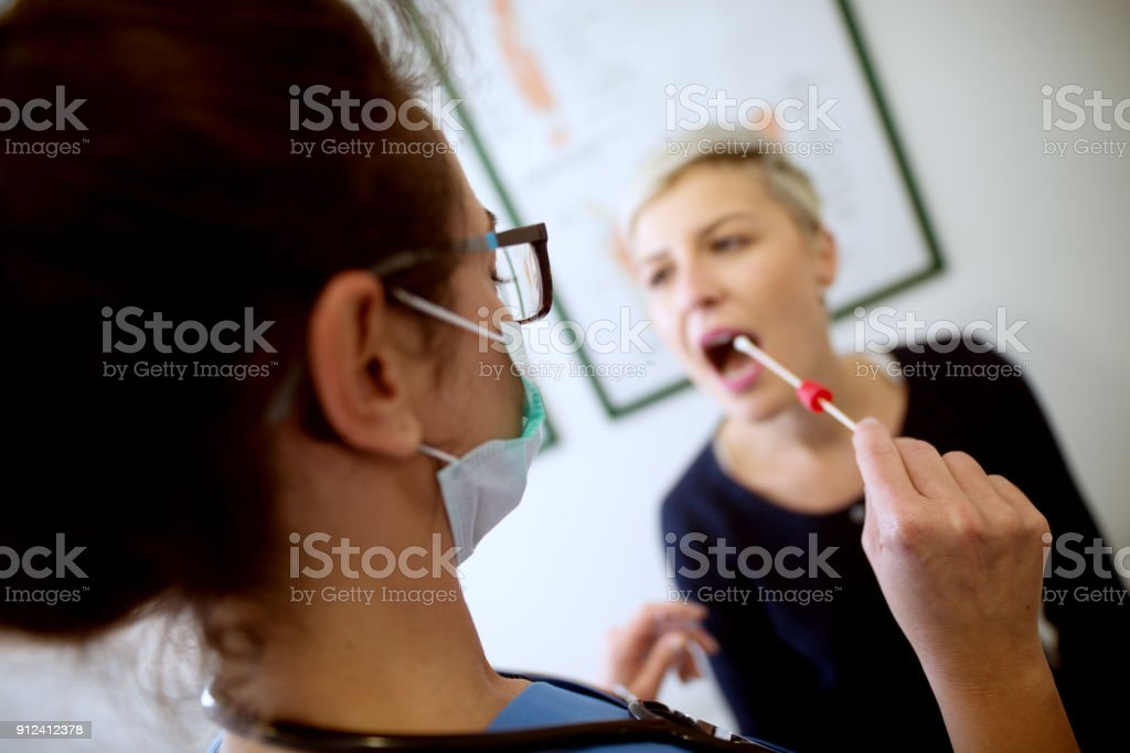 Rear view of woman doctor specialist holding buccal cotton swab and test tube ready to collect DNA from the cells on the inside of a woman patient. stock photo