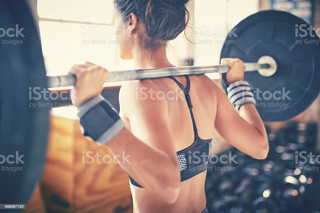 Rear view of woman exercising with barbell in gym ストックフォト