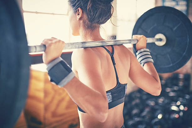 rear view of woman exercising with barbell in gym - weights stock photos and pictures