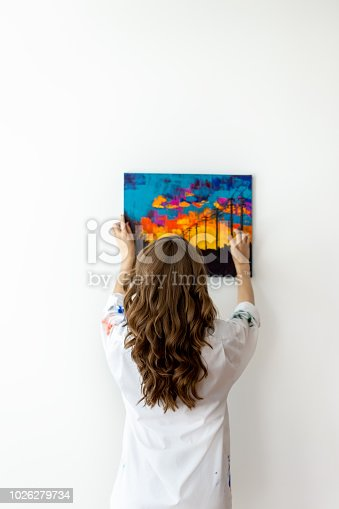 Rear view of young woman hanging picture on the wall
