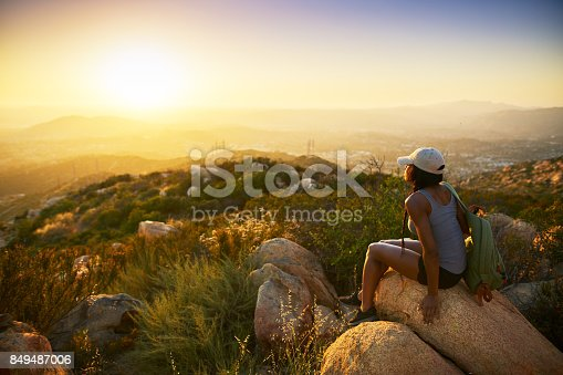 istock Rear view of woman hiker sitting on rock on top of hill 849487006