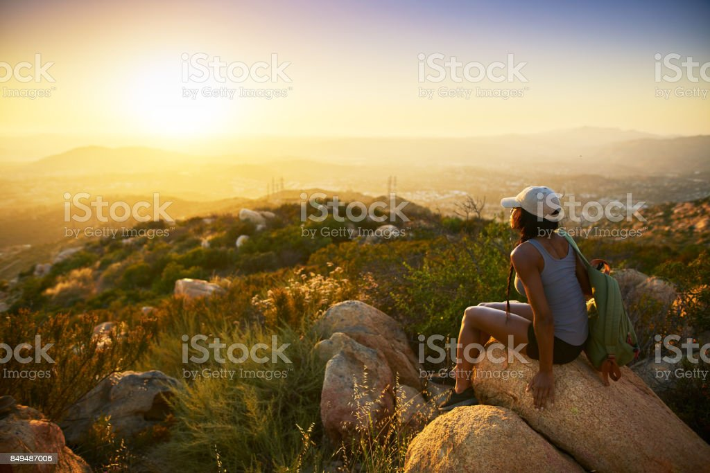 Rear view of woman hiker sitting on rock on top of hill stock photo