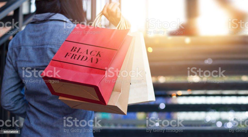Weergave van vrouw met Black Friday boodschappentas terwijl omhoog trappen buiten op de achtergrond winkelcentrum aan de achterkant foto