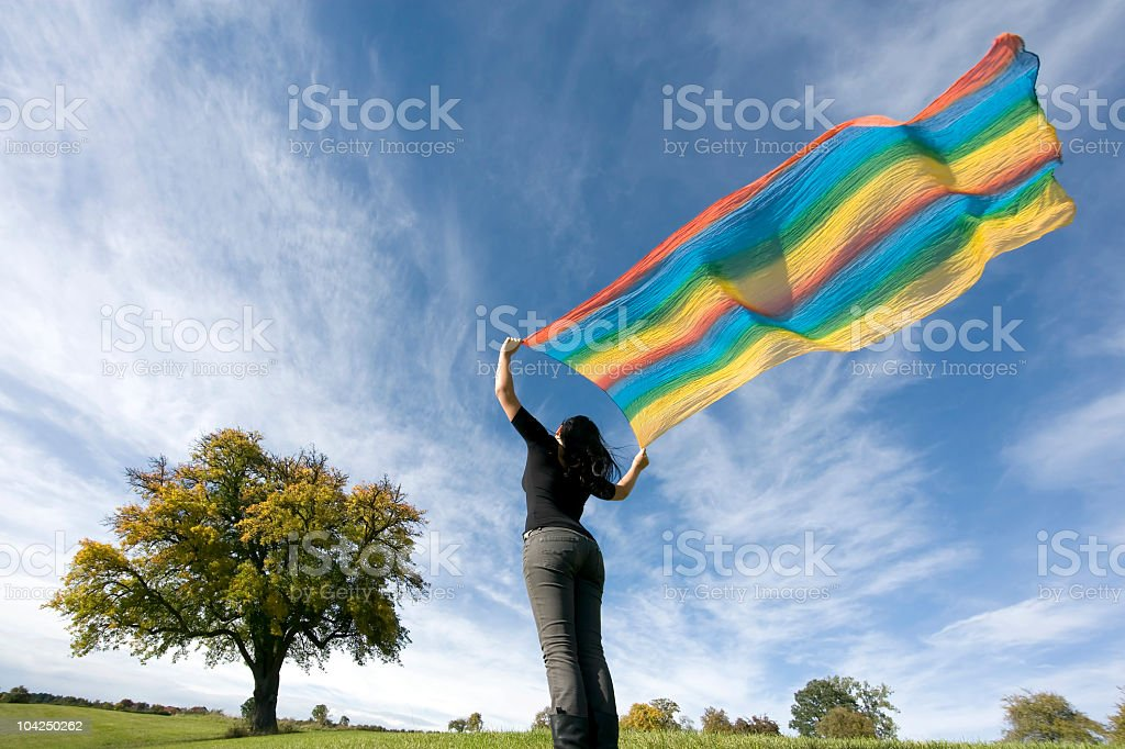 Rear view of woman holding multi colored scarf in wind royalty-free stock photo