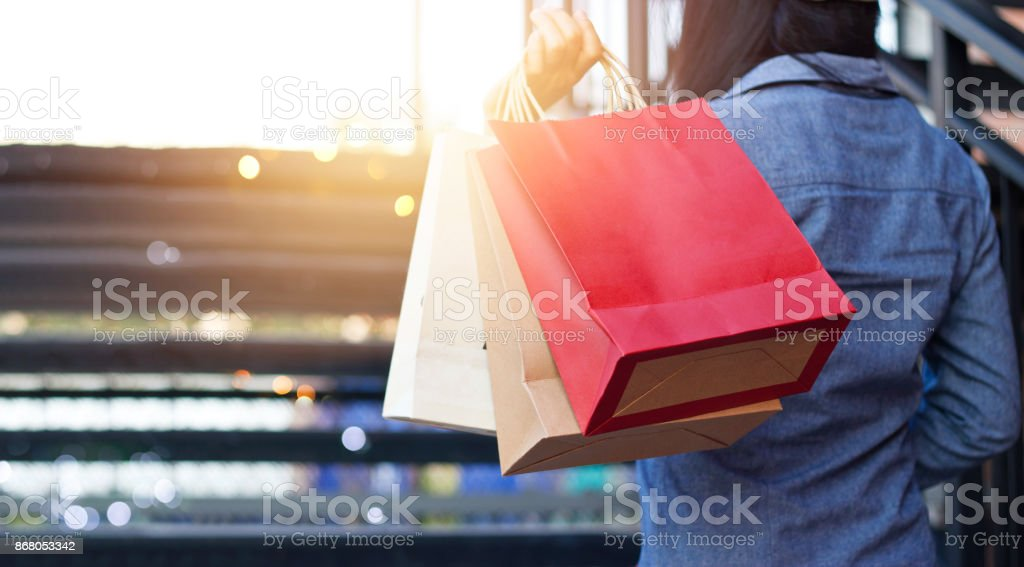 Rear view of woman holding shopping bag while up stairs outdoors on the mall background stock photo
