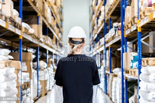 istock Rear view of woman in modern warehouse 513944774