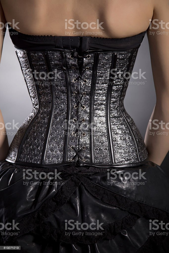 Rear view of woman in silver leather corset stock photo