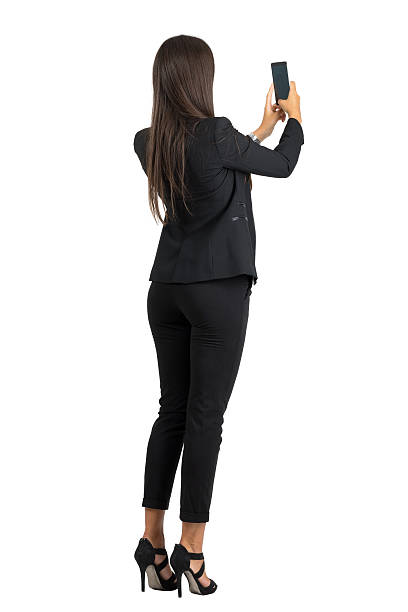 Rear view of woman in suit taking photo with cellphone stock photo