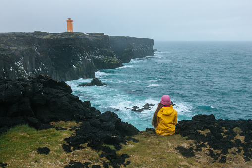 rear view of woman in yellow raincoat sitting on cliff in front of ocean and looking at lighthouse, Iceland