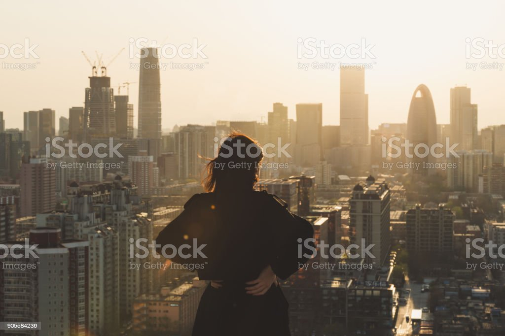 Rear view of Woman looking at city in Sunlight stock photo