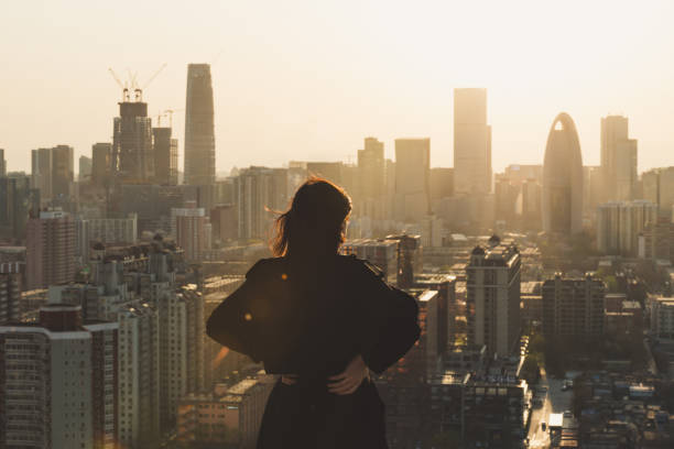 rear view of woman looking at city in sunlight - looking at view stock pictures, royalty-free photos & images