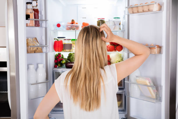 Rear View Of Woman Looking In Fridge Rear View Of Young Woman Looking In Fridge At Kitchen hungry stock pictures, royalty-free photos & images