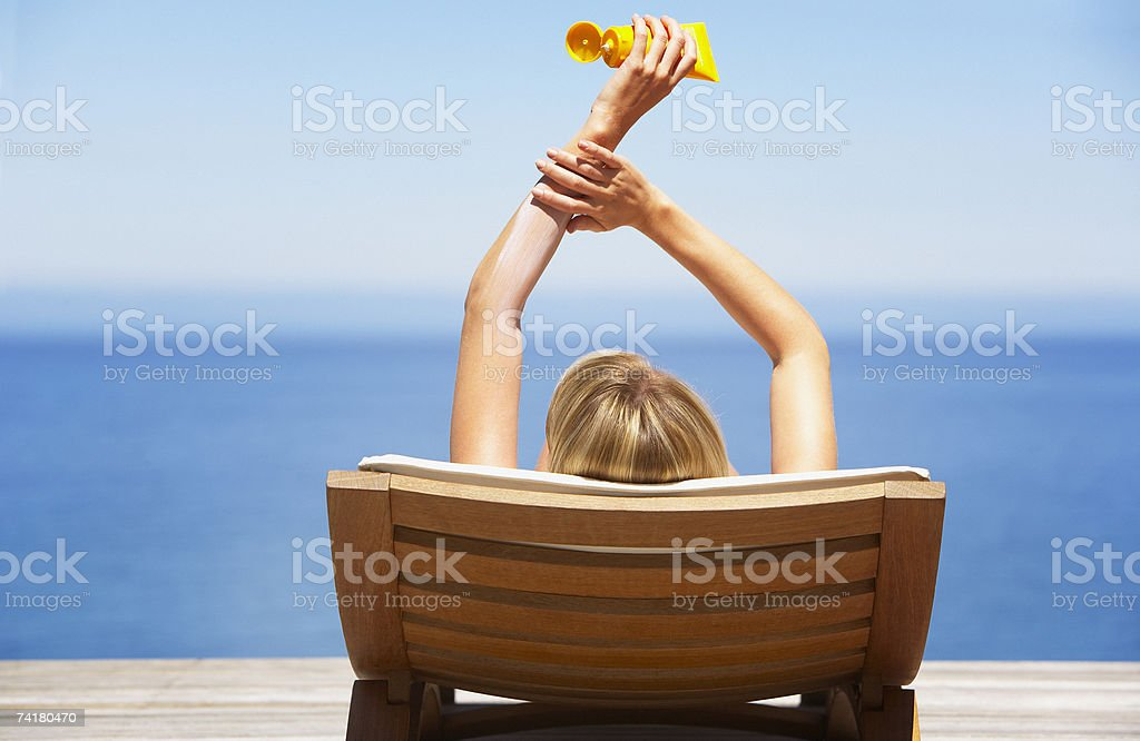 Rear view of woman on folding chair outdoors applying sun block or suntan lotion stock photo
