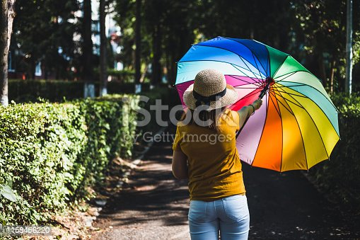 Young woman wearing colorful summer outfit with hat opening colorful umbrella in the park on a sunny day – Hipster girl with rainbow colored sunshade in nature