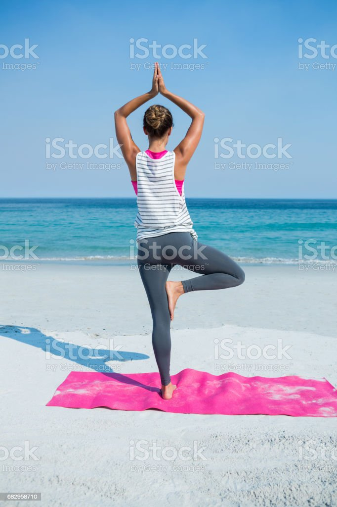 Rear view of woman practicing yoga in tree pose at beach foto de stock royalty-free