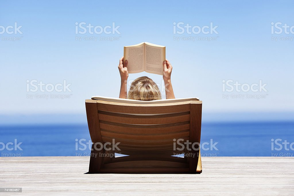 Rear view of woman reading outdoors in wooden chair stock photo